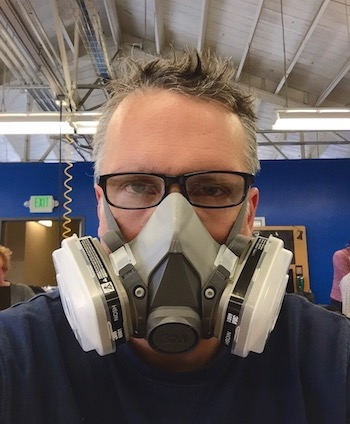 Mark Schmick, grinning behind a dust mask at Techshop SF